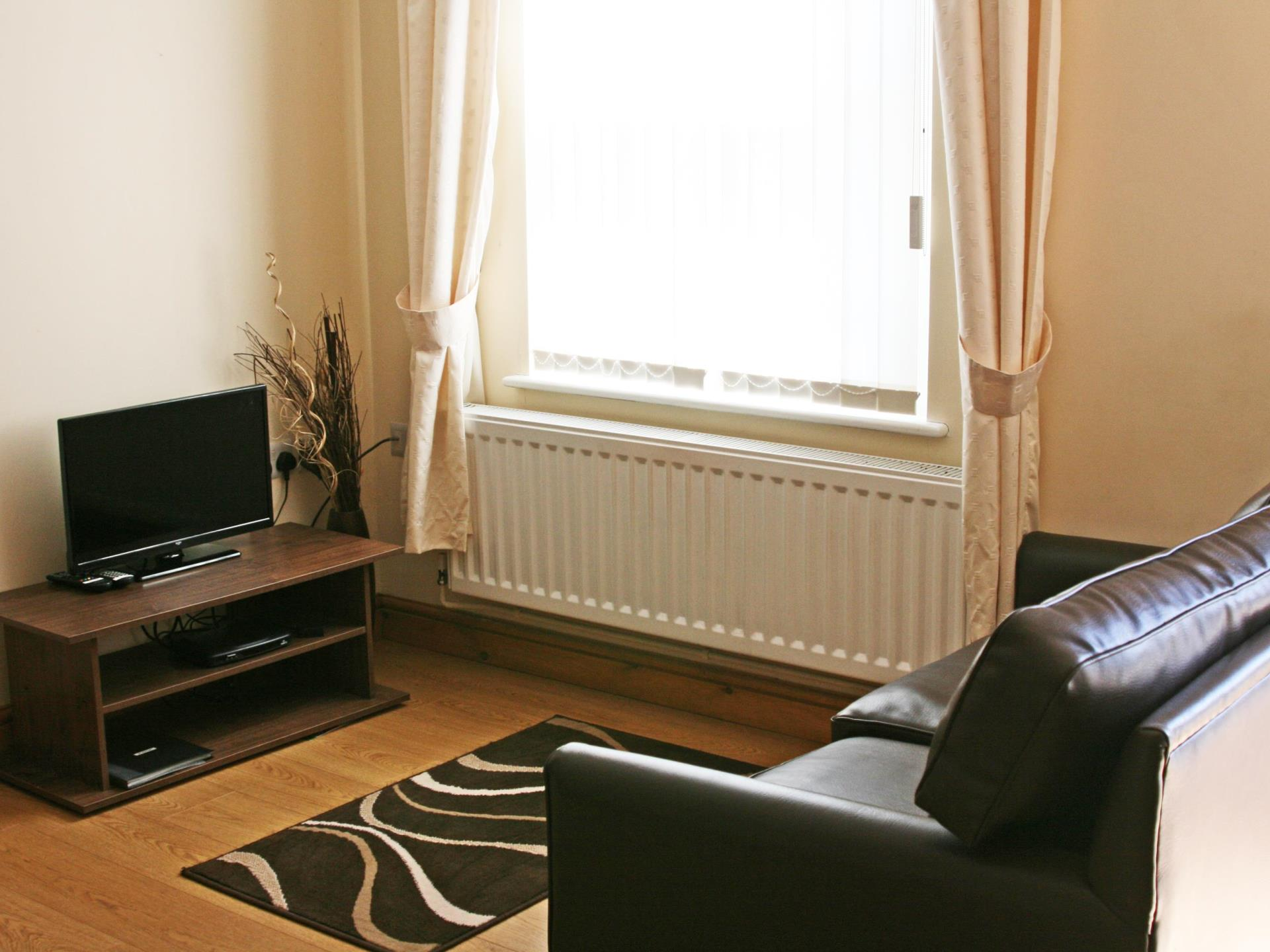 Sofa and TV area in Gremlin Lodge cottages